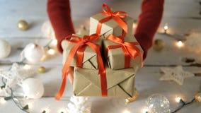Mujer que da las cajas de regalo con la decoración de la Navidad en la tabla de madera blanca almacen de video