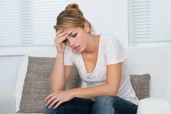 Mujer que da masajes a la cabeza mientras que sufre de dolor de cabeza Imágenes de archivo libres de regalías