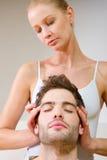 Mujer que da masajes a los templos del hombre Imagenes de archivo