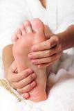 Mujer que da masajes a sus pies Fotos de archivo