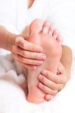 Mujer que da masajes a sus pies Fotografía de archivo libre de regalías