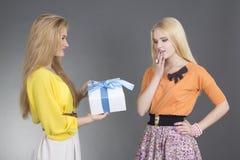 Mujer que da un presente a su amigo sorprendido Foto de archivo libre de regalías