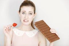 Mujer que decide entre el dulce y la fruta Foto de archivo