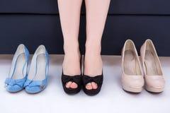Mujer que decide qué zapatos para elegir imagen de archivo