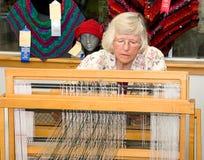 Mujer que demuestra tejer en telar Imagen de archivo