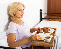 Mujer que desayuna en cama Imagenes de archivo