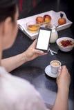 Mujer que desayuna mientras que usa smartphone Imágenes de archivo libres de regalías