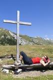 Mujer que descansa bajo cruz de madera Fotos de archivo