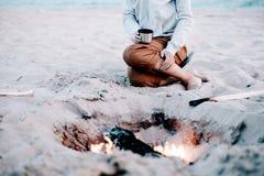 Mujer que descansa cerca de la hoguera en la playa imágenes de archivo libres de regalías