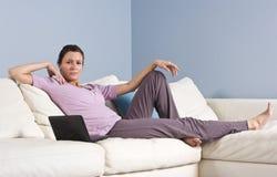 Mujer que descansa en el sofá en el país con la computadora portátil Imágenes de archivo libres de regalías
