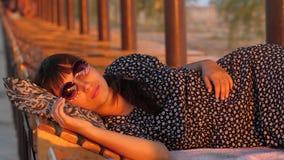 Mujer que descansa en la playa en la puesta del sol metrajes