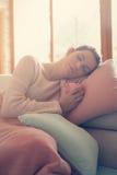 Mujer que descansa sobre el sofá Foto de archivo libre de regalías
