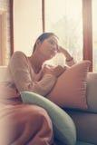 Mujer que descansa sobre el sofá Imagen de archivo libre de regalías