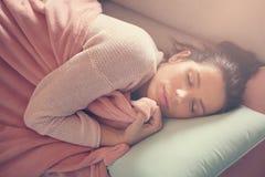 Mujer que descansa sobre el sofá Fotografía de archivo libre de regalías