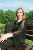 Mujer que descansa sobre un banco en el parque Fotografía de archivo libre de regalías