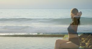 Mujer que descansa sobre un malecón que mira las ondas 4k metrajes
