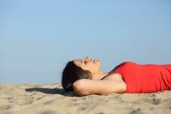 Mujer que descansa y que se relaja en la playa Imagenes de archivo