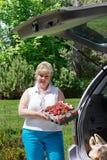 Mujer que descarga las fresas del rectángulo Imagen de archivo libre de regalías