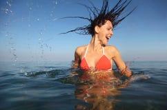 Mujer que desgasta el bañador rojo que hace girar en el mar Imagen de archivo