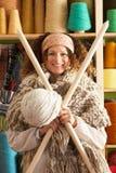 Mujer que desgasta la bufanda hecha punto que sostiene agujas gigantes Imagen de archivo