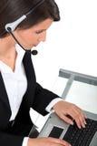 Mujer que desgasta un receptor de cabeza que pulsa en un teclado Imagenes de archivo