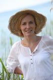 Mujer que desgasta un sombrero de paja Foto de archivo