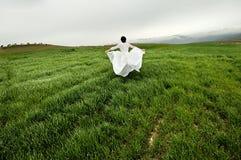 Mujer que desgasta una alineada de boda que se ejecuta en el campo Imagen de archivo