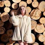 Mujer que desgasta una capa blanca en troncos del álamo Imagenes de archivo