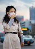 Mujer que desgasta una máscara en el tráfico Imagen de archivo libre de regalías