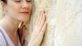 Mujer que desliza la mano contra la pared de piedra vieja en la cámara lenta Superficie áspera conmovedora de la mano femenina de almacen de video