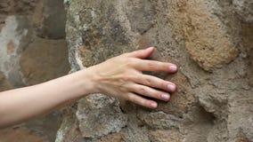 Mujer que desliza la mano contra la pared de piedra vieja en la cámara lenta Superficie áspera conmovedora de la mano femenina de almacen de metraje de vídeo