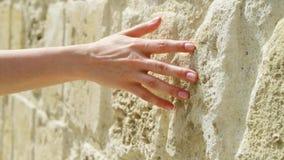 Mujer que desliza la mano contra la pared de piedra vieja en la cámara lenta Superficie áspera conmovedora de la mano femenina de metrajes
