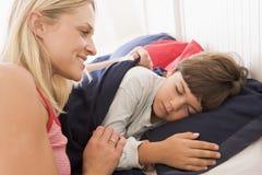 Mujer que despierta al muchacho joven en la sonrisa de la cama Fotos de archivo libres de regalías