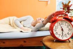 Mujer que despierta apagando el despertador por mañana Foto de archivo libre de regalías