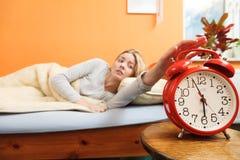 Mujer que despierta apagando el despertador por mañana Imagen de archivo libre de regalías