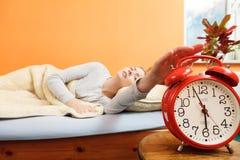 Mujer que despierta apagando el despertador por mañana Imagenes de archivo