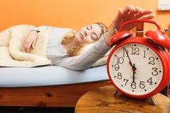 Mujer que despierta apagando el despertador por mañana Fotografía de archivo