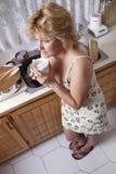Mujer que despierta con un café Foto de archivo libre de regalías