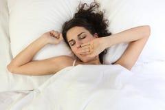 Mujer que despierta en cama foto de archivo libre de regalías