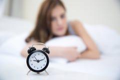 Mujer que despierta por la mañana y que mira en el despertador Imagen de archivo