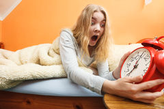 Mujer que despierta tarde apagando el despertador Imagen de archivo