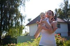 Mujer que detiene al bebé en los brazos contra una casa Foto de archivo