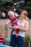 Mujer que detiene al muchacho gritador gruñón del niño al aire libre Imagen de archivo