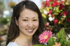 Mujer que detiene las flores en cierre del retrato del cuarto de niños de la planta Fotografía de archivo libre de regalías