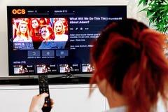 Mujer que detiene un telecontrol de la TV y a las muchachas del reloj, una creación original de la industria de HBO Las muchachas imágenes de archivo libres de regalías