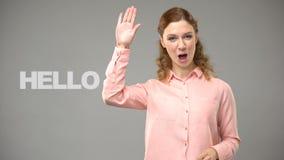 Mujer que dice hola en el lenguaje de signos, texto en el fondo, comunicación para sordo almacen de metraje de vídeo