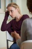 Mujer que discute problemas con el consejero foto de archivo