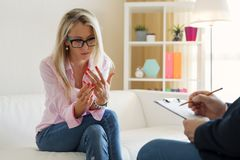 Mujer que discute problemas de la relación en la oficina del terapeuta foto de archivo libre de regalías
