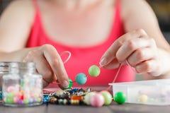 Mujer que diseña el collar colorido con las gotas plactic Imagenes de archivo