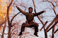Mujer que disfruta de actividad en un parque de la cuerda foto de archivo